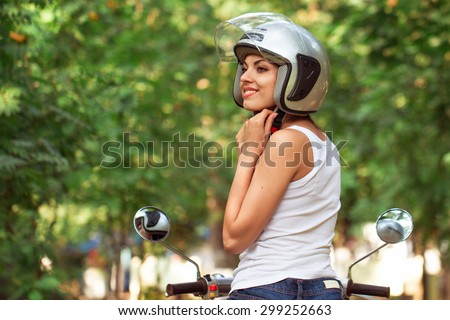Attractive woman riding on a moped wearing helmet - stock photo