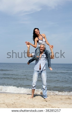 Attractive woman riding on man's shoulders on the beach - stock photo