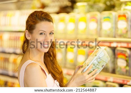 Attractive woman shopping in supermarket. Closeup portrait beautiful young woman picking up, choosing green leafy salad in grocery store. Positive face expression emotion feeling healthy life style - stock photo