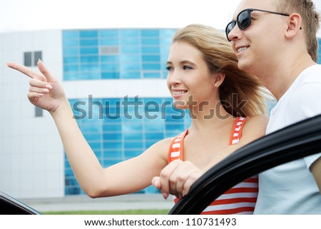 Attractive woman showing something to man and putting her hand on the door of car - stock photo
