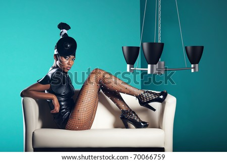 Attractive woman siting in white chair with chandelier - stock photo