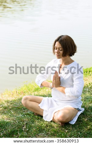 Attractive woman sitting in miditation pose called sukhasana at the river-bank. Her eyes are closed, the hands are folded as she prays. Woman wears white cotton clothes. River at the background - stock photo