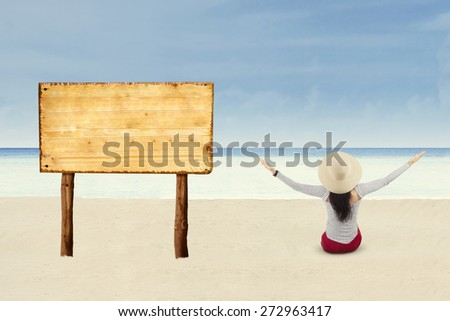 Attractive woman sitting next to billboard on beach - stock photo