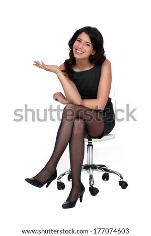 Attractive woman sitting on a chair - stock photo