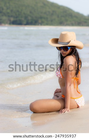 Attractive woman sitting on beach - stock photo