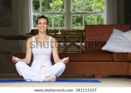 Attractive woman sitting on floor at home in yoga position  - stock photo