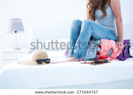 Attractive woman sitting on her case at home in the bedroom - stock photo