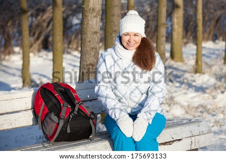 Attractive woman sitting on park bench at winter season - stock photo