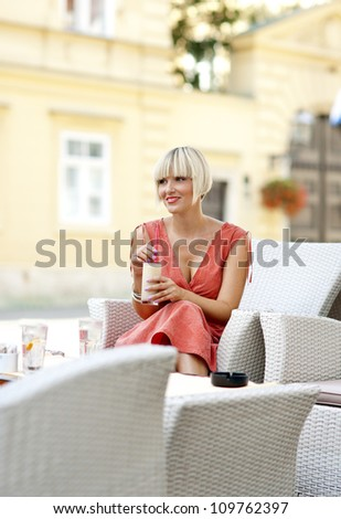 attractive woman sitting with coffee in outdoor cafe chair - stock photo