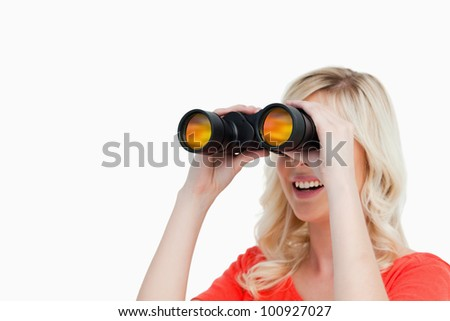 Attractive woman smiling while looking on the side with binoculars - stock photo