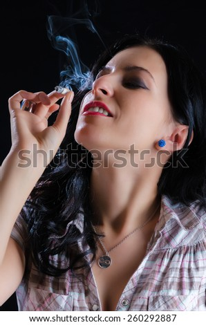 Attractive woman smoking a cannabis joint against a black background - stock photo
