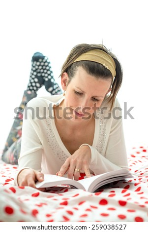 Attractive woman spending a relaxing day at home lying on a colorful red polka dot counterpane on her bed reading a novel. - stock photo