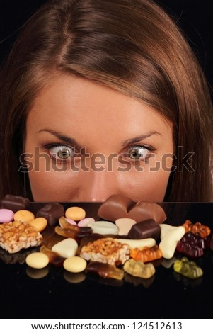 Attractive Woman starring on sweets on a table - stock photo