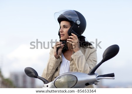 Attractive woman takes off her helmet - stock photo