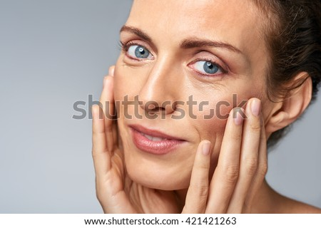 Attractive woman touching her face, mature beauty concept - stock photo