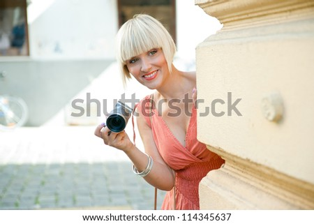 attractive woman tourist with camera hiding behind wall - stock photo