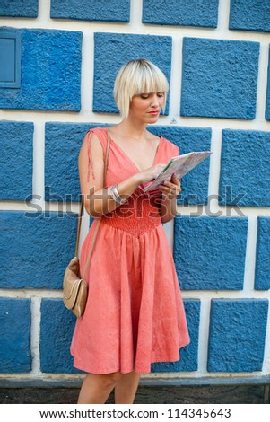 attractive woman tourist with city map on the street corner - stock photo