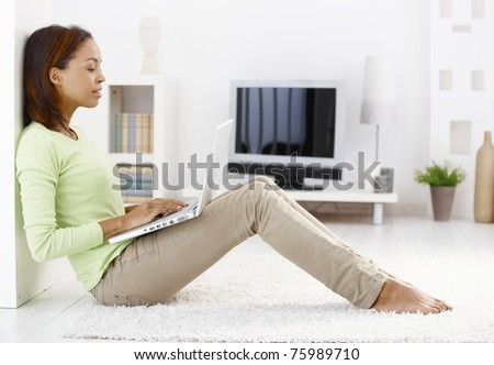 Attractive woman using laptop computer, sitting on floor of living room, smiling.? - stock photo