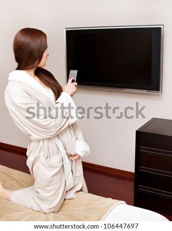 Attractive woman watching TV in bedroom - stock photo
