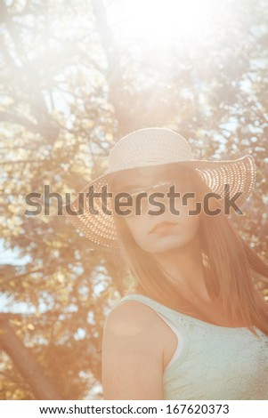 Attractive woman wearing a sun hat and sunglasses in the summer. - stock photo