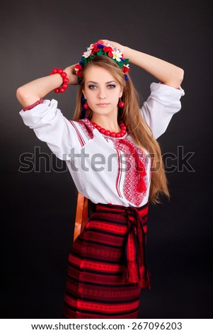 Attractive woman wears Ukrainian national dress isolated on a black background - stock photo
