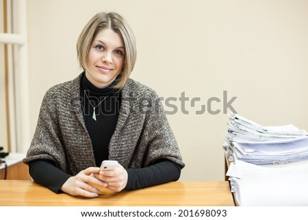 Attractive woman with cellphone in hands sitting at the table, copyspace - stock photo