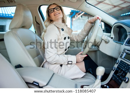 attractive woman with glasses sitting in car driver seat - stock photo