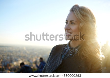 Attractive woman with good mood enjoying beautiful city view while standing on a roof of a of high building, gorgeous smiling female relaxing after walking outside in warm spring day during free time - stock photo