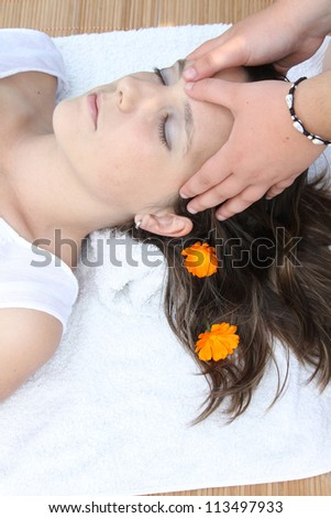 attractive woman with hot stones treatment at a spa - stock photo