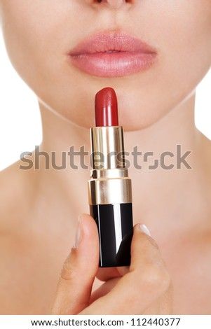 Attractive woman with luminous dark eyes applying red lipstick to her lips. Isolated on white - stock photo