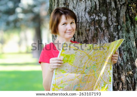 Attractive woman with map under a tree  - stock photo