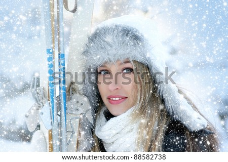 Attractive woman with ski over winter background - stock photo