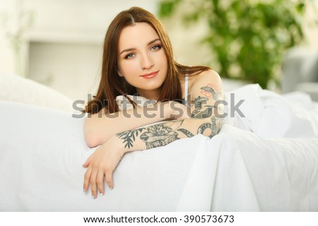 Attractive woman with tattoo lying on the bed - stock photo