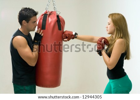 Attractive woman working out with boxing gloves and a heavy punching bag with her trainer. - stock photo