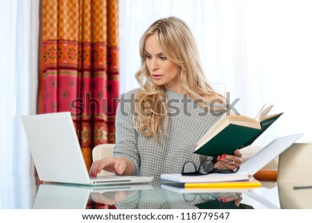attractive woman writer in her home with laptop - stock photo