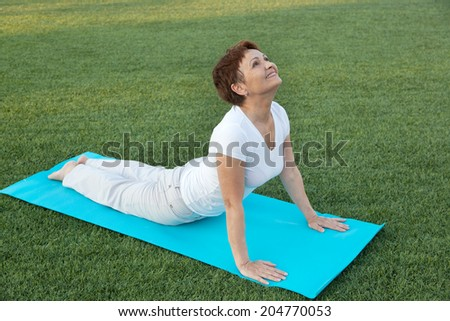 attractive woman 50 years doing fitness, outdoors - stock photo
