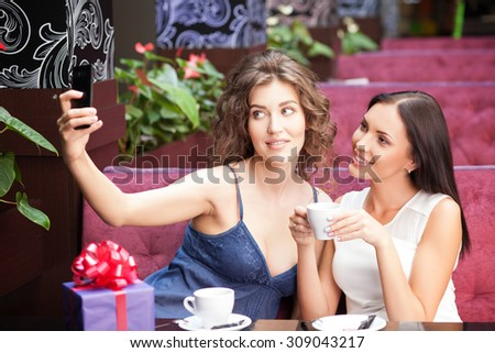 Attractive women are making selfie in cafe. They are sitting at the table and drinking coffee. The friends are looking at the mobile phone and smiling. There is a box of gift on the table - stock photo