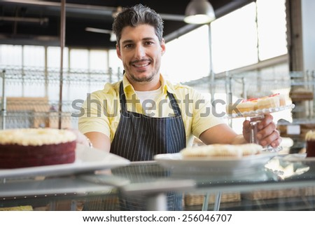 Attractive worker in apron posing at the bakery - stock photo