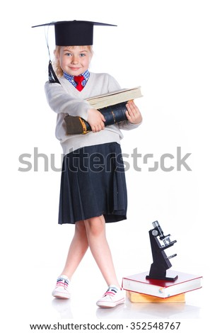 Attractive 5 year old girl in  large graduation cap with book and microscope over white background - stock photo
