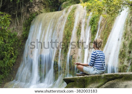 Attractive youn woman during meditation near the waterfall, Java, Indonesia - stock photo