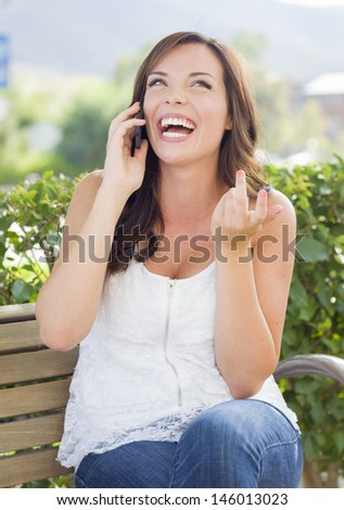 Attractive Young Adult Female Talking on Cell Phone Outdoors on Bench. - stock photo