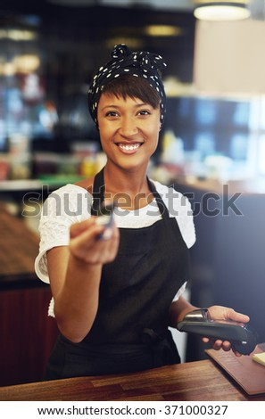 Attractive young African American business owner returning a credit card to a customer after processing payment for a sale, focus to her face and friendly smile - stock photo