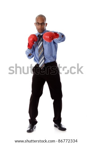 Attractive young African American businessman wearing boxing gloves. Blow with left arm. Studio shot. White background. - stock photo