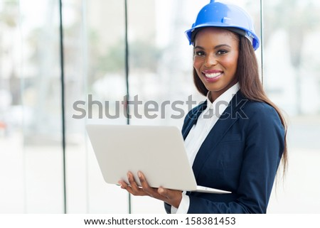 attractive young african architect using laptop in office - stock photo