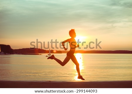 Attractive young African girl athlete running at sunset or sunrise along the beach. Fitness training of runner. - stock photo
