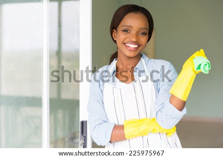 attractive young african girl holding dishcloth - stock photo