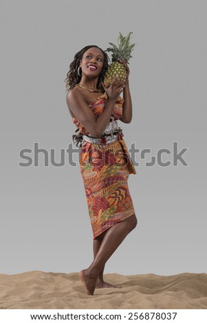 Attractive young african woman carrying pineapple on sand on gray studio background - stock photo