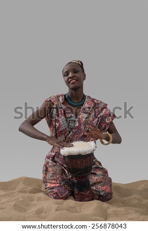 Attractive young african woman playing traditional drum on sand on gray studio background - stock photo