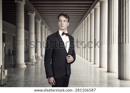 Attractive young and posh man in a castle with many columns - stock photo