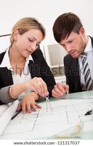 Attractive young architects working on their blueprint - stock photo